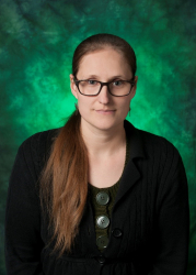 Picture of Staff Senate Katie Hebert. Katie has dark glasses, brown colored eyes and a long brown ponytail. Katie is against a green background and is wearing a black blazer with large circular buttons in the center